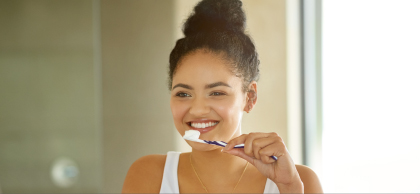 young woman brushing teeth with whitening toothpaste