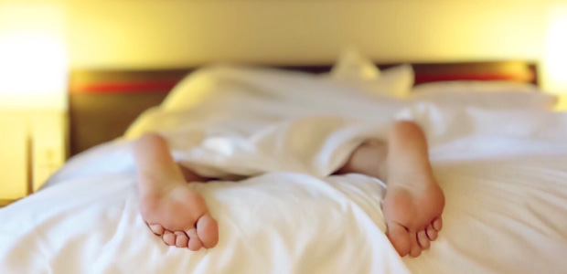 two feet poking out of white bedsheets