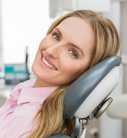 woman with blonde hair in a light pink shirt smiling as she lays back in the dental chair