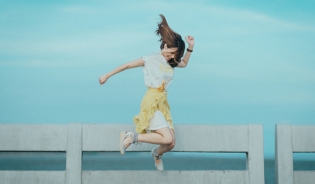 Brunette woman in a yellow and white spring dress jumps on an ocean pier because she has great oral and overall health