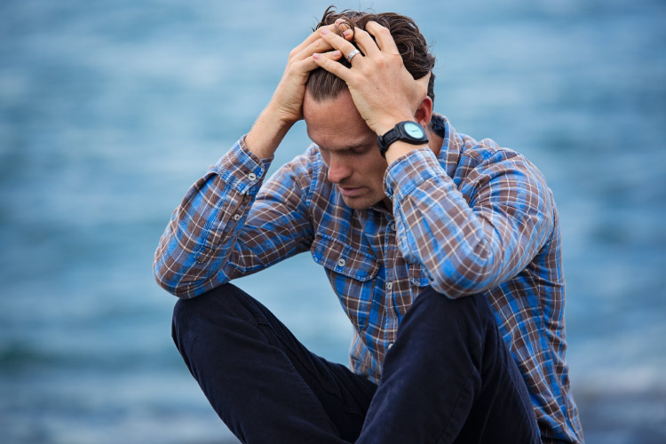 A brunette man by the ocean in a blue and red plaid shirt clutches his head in pain due to a chronic headache