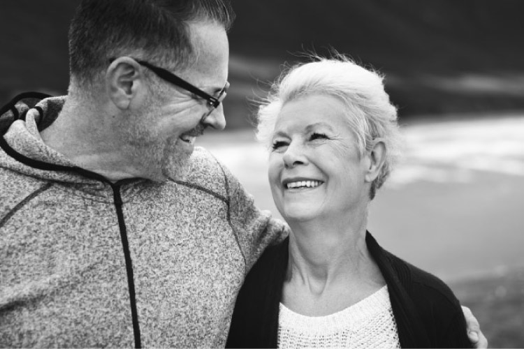 elderly couple smile at each other knowing their oral health care is on track