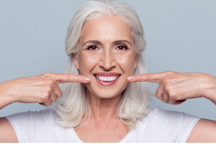 white haired woman points to her porcelain veneers with both fore fingers