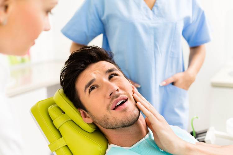 young man in the dentist's chair getting an exam and cleaning