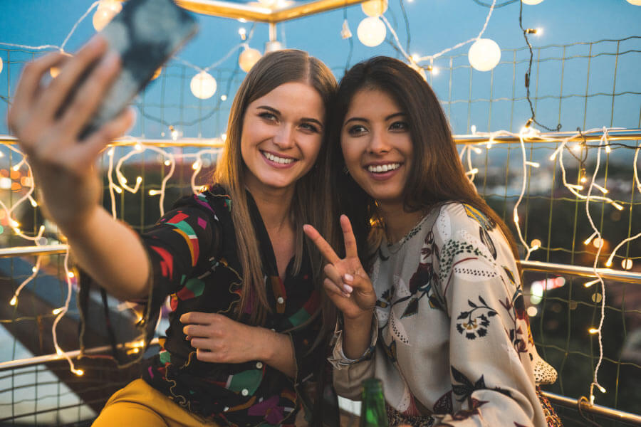 Two girls smile while taking a selfie after professional teeth whitening in San Antonio, TX