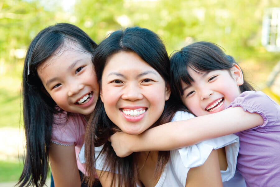 Mom smiles while giving a piggy-back ride to her 2 daughters outside before visiting their family dentist