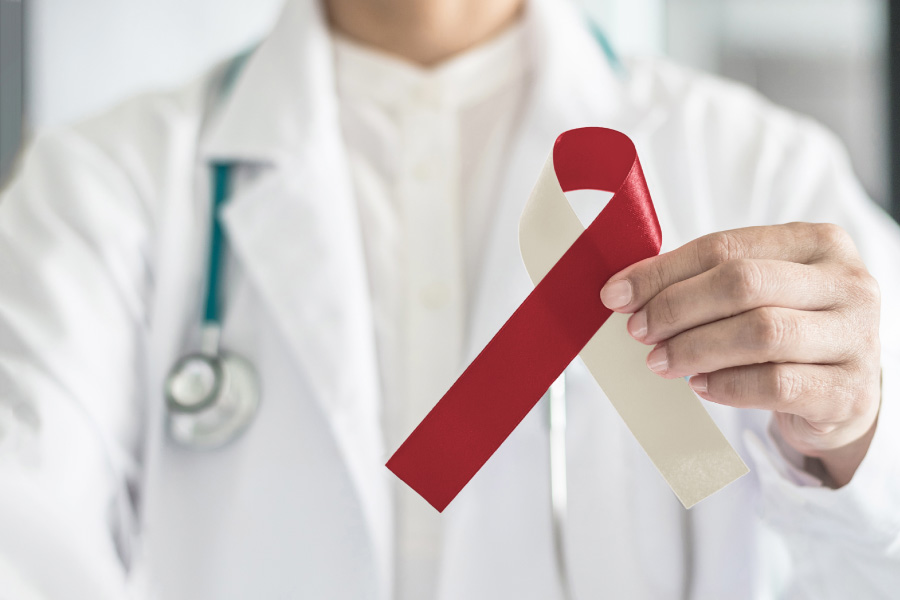 A healthcare professional holds up a burgundy and ivory ribbon to indicate oral cancer awareness