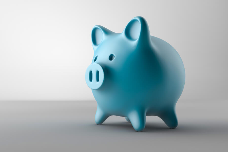 A blue piggy bank for saving money against a gray background for a post about affordable dental care in San Antonio, TX